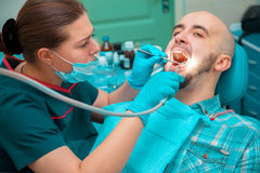 Nice man makes prevention of caries on dental checkups Stock Photos