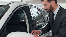 Nice man planning to buy car. Young man carefully viewing model, inspecting side door and glass. Nice man planning to buy car. Young man carefully viewing model stock footage