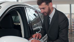Nice man planning to buy car. Young man carefully viewing model, inspecting side door and glass. Nice man planning to buy car. Young man carefully viewing model stock video footage