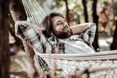 Nice man resting in a white hammock