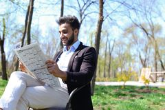 Mulatto guy reading newspaper in caf and smiles. Royalty Free Stock Images