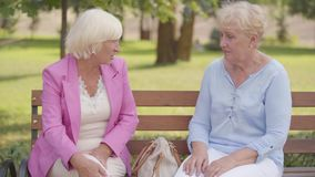 Nice mature caucasian women sitting at the bench in the summer park. Senior woman with blond hair complaining the pain. In the knee to her friend. Elderly stock video