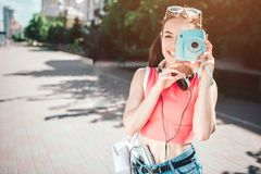 Nice melomanic girl is looking at camera though lenz of her camera. She is smiling. Girl has headphons around her neck. And music player close to her body. She Stock Photo
