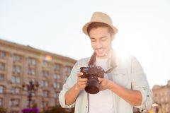 Nice memories of summer vacation! Young male tourist with a digi. Tal camera is checking the photos he took outside, with beaming smile, excited Royalty Free Stock Photography