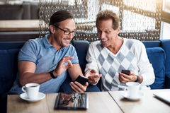 Nice men using smart phones. Ok. Happy and positive male colleagues drinking coffee and using smart phones royalty free stock images