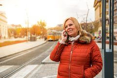 Nice woman on the street. A nice middle age woman standing at a tram station in a winter jacket and speaking on her smartphoner Stock Photo