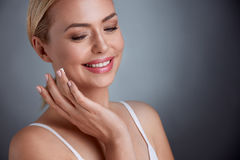 Nice middle aged woman  applying face cream. Joyfully smiling Stock Photography