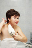 Nice middle aged woman dries her hair in the bathroom Royalty Free Stock Photos