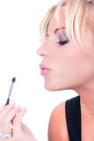Nice model applying makeup with brush Stock Image