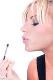 Nice model applying makeup with brush Stock Image