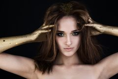 Nice Model Woman with Perfect Makeup and Brown Hair. And Golden Hand royalty free stock photos