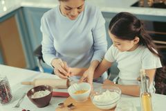 Nice mother cooking scrambled eggs with her daughter stock photo