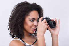 Nice mulatto woman taking photos. It is my hobby.  Pleasant content mulatto woman holding photo camera while taking photos Royalty Free Stock Photos