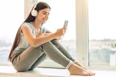 Pretty teenage girl listening to music on window sill. Nice music. Charming teenage girl with long hair sitting on the window sill and listening to the music in Royalty Free Stock Photo