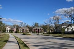 Nice Neighborhood. Street leading into an upscale subdivision with large brick homes. Open blue sky provides space for copy Stock Photo