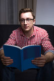 Nice nerdy bookworm. Seating on couch Royalty Free Stock Image