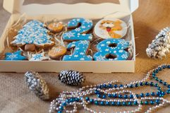 Nice new year set of honey cookies, glazed by blue, white cream near different decorations royalty free stock image