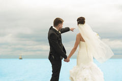 Nice newlyweds are standing by the ocean shore. Stock Image