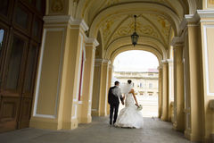 Nice newlyweds are walking under church  arches. Royalty Free Stock Images