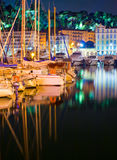 Nice Night. Image of yacht parked with a beautiful reflection of the city at night. In the background are seen the lights of the park in Nice, France Royalty Free Stock Images