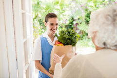 Nice nurse bringing vegetables to old patient Royalty Free Stock Image