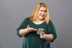 Nice obese woman pointing at her smartphone. Digital device. Nice obese woman standing against grey background while pointing at her smartphone Stock Photo