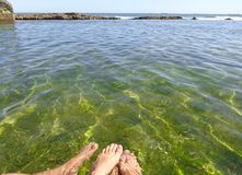 Feet of a couple in crystal clear sea water with depth of field and space for editing royalty free stock photos
