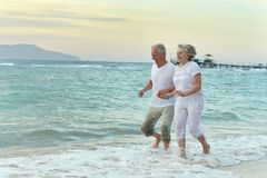 Nice old couple at resort. Nice old couple running on sea beach Royalty Free Stock Images