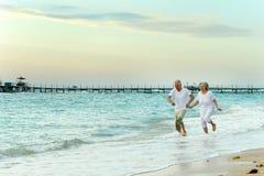 Nice old couple. Running on sea beach stock photos