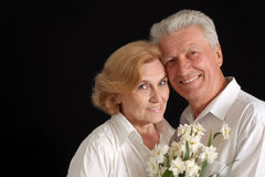 Nice old people with flowers. On the black background Stock Photography