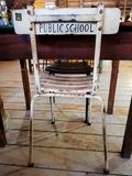 A nice old study chair in front of a desk with the words public school printed on the back royalty free stock photos