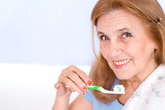 Nice old woman brushing her teeth Stock Photos