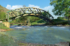 Nice old wooden arc bridge on river. Nice wooden arc bridge lower view Royalty Free Stock Photo