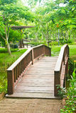 Nice old wooden bridge in park at summertime. Stock Image