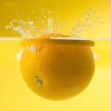Nice orange falling into water. Yellow background. Ripe orange falling into water, splashes all around Royalty Free Stock Photo