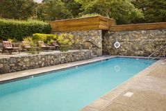 Outdoor swimming pool with seating Royalty Free Stock Photography