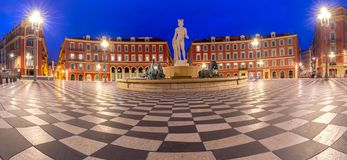 Nice. Panorama of Massena Square and the fountain in the night lighting. Panorama of Massena Square, the facades of old houses and a fountain at dawn. Nice royalty free stock image