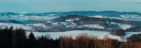 Nice panoramatic Czech winter landscape with hill, trees and blue sky royalty free stock photography