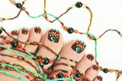 Nice pedicure. Nice pedicure with rhinestones on female legs embellishment from beads on a light background Stock Photo