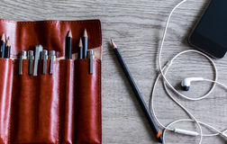 Nice pen leather housing with a phone and earphones on a gray ba Stock Photography