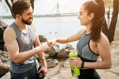 Nice people are standing in front of each other and touching their fists. Also they are looking to each other and. Smiling. Girl is holding a bottle of water Stock Photo
