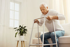 Nice persistent man standing up from the sofa. I will do it. Nice persistent senior man standing up from the sofa and trying to walk while using a walking frame Stock Photo