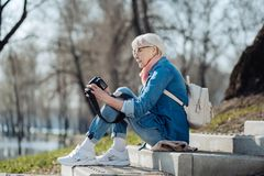 Inspired woman holding her camera. Nice photos. Alert mature woman sitting on the steps and looking through photos Stock Image