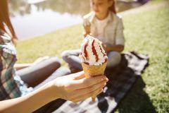 Nice picture of adult holding con of ice cream in hand. There is a girl sitting besides adult and holding con of icream royalty free stock images