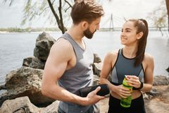 Nice picture of attractive couple standing at the river shore. THey are looking to each other and smiling. Girl is. Holding a bottle of water while the guy is Stock Images