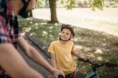 Nice picture of cheerful child looking up on his father. He is standing at his bicycle. Adult guy is standing besides. His son and looking at him Stock Photo