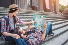 Nice picture of young tourists on stairs. She sits there and points on map. He holds map and lies on woman`s knees. stock images