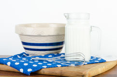 Nice pitcher of milk with bowl and whisk Stock Image