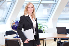 Nice place of work. Female employee in her place of work and with her laptop in her hands Royalty Free Stock Image