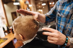 Nice pleasant barber combing the boys hair. From the top of the head. Nice pleasant professional barber holding a comb and combing the boys hair while standing stock photos
